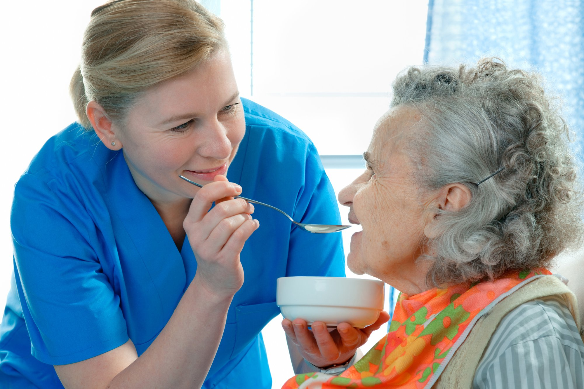 A female caregiver provides in-home assistance for an elderly woman by feeding her a healthy meal.